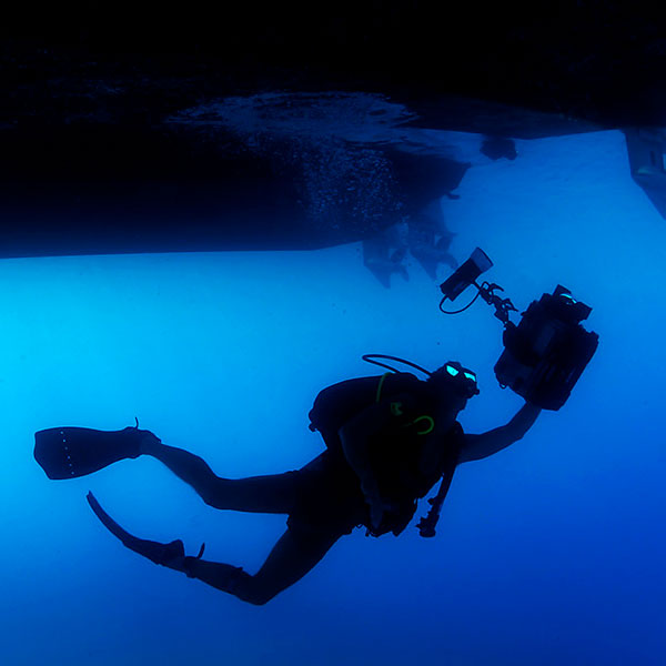 diver with camera under boat ibiza