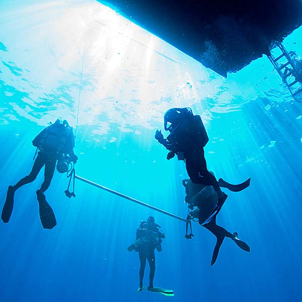 divers under boat ibiza